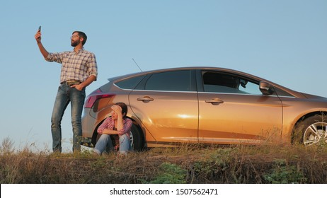 Couple traveling by car catches a phone signal while standing on the side of the road