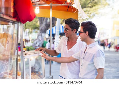 Couple traveling in latin america, buying street food in a truck. Isla Mujeres, Mexico.