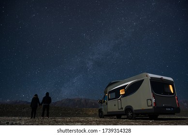 Couple traveling with a motorhomes parked Under Milky Way near Lake Tekapo, New Zealand. Travel campervan milky way.