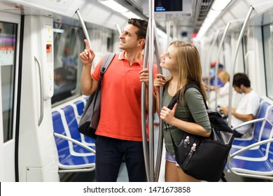 Couple is traveling and moving around the city using the metro.
