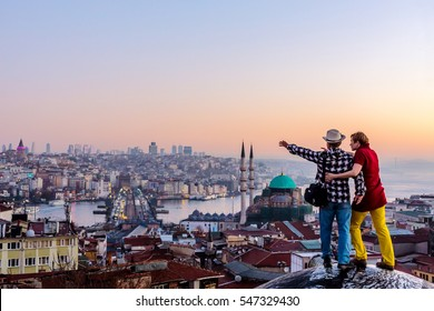 Couple traveling together in bright casual Clothing shirts dress and jeans pants overlooking eastern City from top of Building pointing with hands