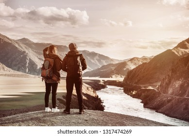 Couple of travellers stands on viewpoint and looks at mountains and river from viewpoint. Travel concept with space for text