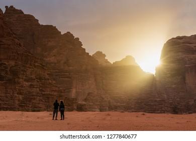 Couple travelling in Wadi Rum desert in Jordan, enjoying beautiful sunrise in the morning