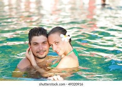Couple in tropical swimming pool