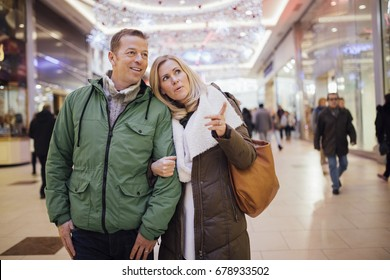 A couple trying to find something new for a christmas presents at a shopping centre.