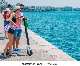 A Couple is trying to rent an e scooter parked on a boardwalk next to the sea.
