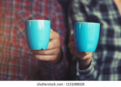 couple with two cups of morning coffee in plaid shirts