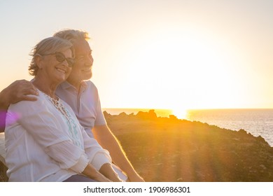 couple of two cute seniors together enjoying summer and having fun at the beach looking at the sea or ocean with sunset - mature people having a good lifestyle - Shutterstock ID 1906986301