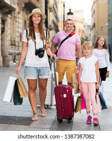 Couple with two kids travelling together on city, walking with baggage