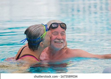 couple of two seniors doing exercise together to be and have a healthy and fit lifestyle - pensioners and mature people swimming in the pool and woman kissing the man