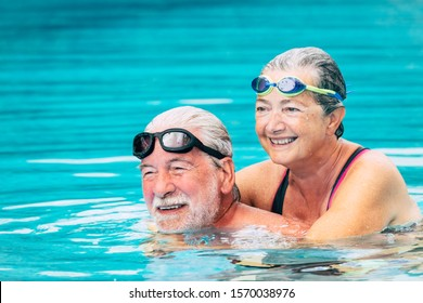 couple of two seniors hugged in the water of swimming pool - active man and woman doing exercise together at the pool - hugged with love - wearing goggles