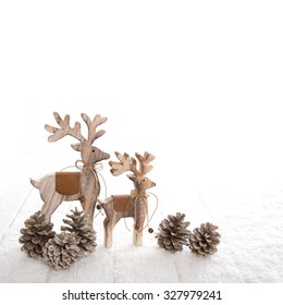 Couple of two wooden deer with fir cone on white wooden background for christmas decoration.