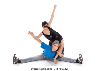 A couple of two young, attractive, modern ballet dancers, one woman and one man,  in dynamic action figure, on white background, studio image.
