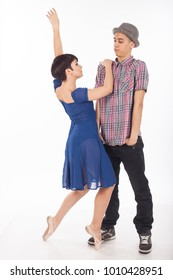 A couple of two young dancers, attractive ballerina wearing blue transparent dress, on pointes and handsome man wearing a pink checkered shirt and a hat. Studio image on white background.