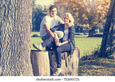 Couple of two young people in love sitting on a wood at autumn park in sunny day looking at the camera. Horizontally.
