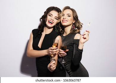 Couple of Two Young Rich Women Laughing with Crystal of Champagne. Luxury. Party time.