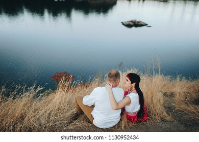 A couple in Ukrainian national clothes romantic embrace near the river. Ukrainian wedding in ethnic traditions. Zaporozhye Cossack. View from the back.
