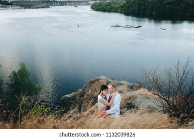 A couple in Ukrainian national clothes romantic embrace near the river. Ukrainian wedding in ethnic traditions. Zaporozhye Cossack. Khortytsya.