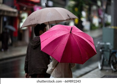 Couple with umbrellas on a rainy day in Tokyo.