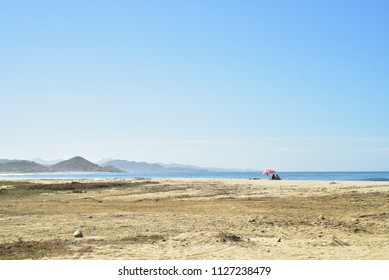 couple under beach tent in vast Baja beach landscape