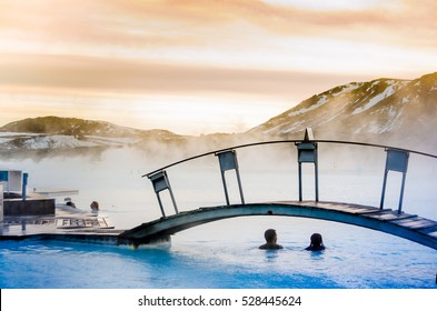 a couple under the bridge in the thermal blue lagoon, Iceland