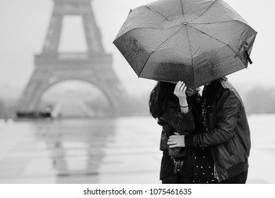 Couple under the rain, covered with black umbrella. Lovers hide their faces with umbrella. Trocadero, Paris