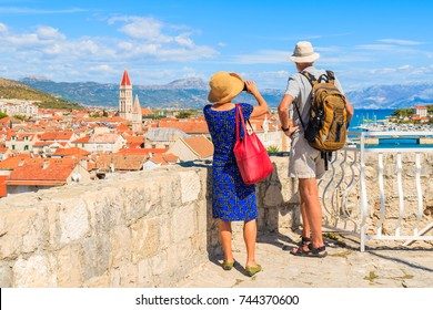 Couple of unidentified elderly tourists taking picture of Trogir town from castle walls, Dalmatia, Croatia