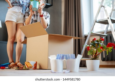 Couple unpacking box. Close up of just married couple unpacking home plants moving to new house