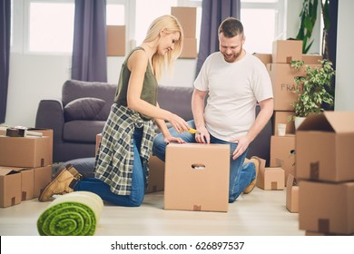 Couple unpacking boxes in new apartment