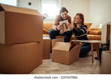 Couple unpacking boxes with their stuff in new home