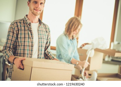 Couple unpacking cardboard boxes in their new home. Young couple.