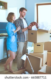 Couple unpacking cardboard boxes in their new home
