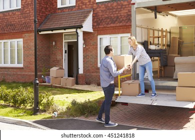 Couple Unpacking Moving In Boxes From Removal Truck