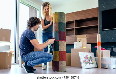 Couple unpacking moving boxes and unrolling the carpet