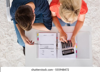 Couple Using Calculator For Calculating Invoice, Tax, Bills And Retirement Money On Desk At Home