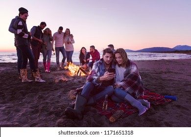 Couple using cell phone during autumn beach party with friends drinking beer and having fun