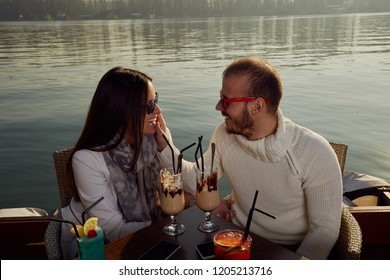 Couple using cellphone while drinking coffee outdoors.