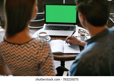 Couple Using Computer, Working From Cafe. Young Male And Female Students Studying, Looking On Green Screen Of Laptop And Making Notes In Copybook Sitting In Coffee Shop. Internet Learning