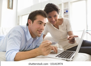 Couple using credit card shopping on line. Laptop.indoor
