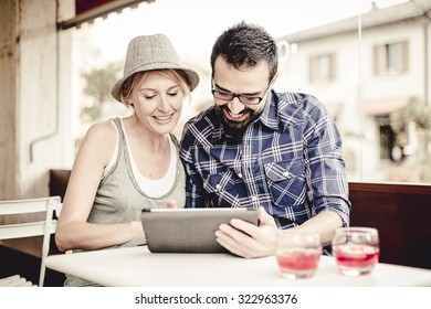 Couple using a digital tablet at the bar.