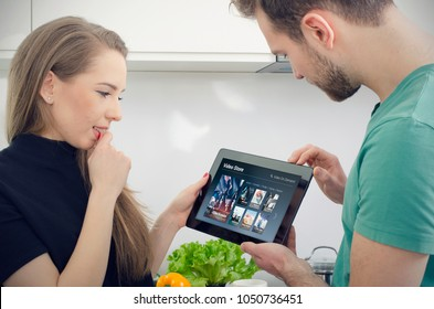 Couple using digital tablet for watching movie on VOD service. Video On Demand television internet stream multimedia concept