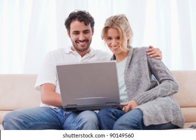 Couple using a laptop in their living room