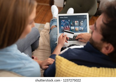 Couple using laptop for watching movie on VOD service. Video On Demand television subscription buy with credit card