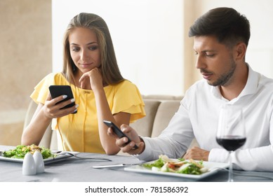 Couple Using Phones On Dinner In Restaurant. Young Man And Woman Looking On Mobile Phones Feeling Bored On Boring Date In Restaurant. Communication Problems. High Quality Image.