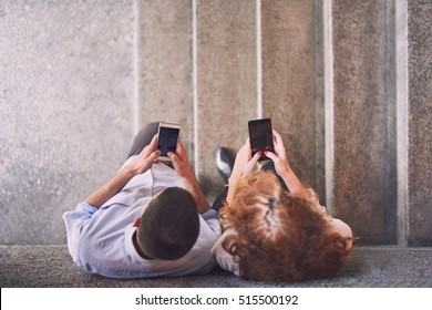 Couple using smart phones leaned on the wall, focus on the phones