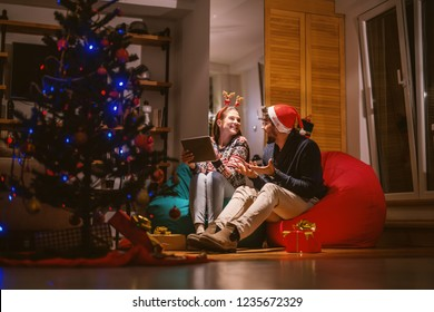 Couple using tablet while sitting in bean bags. On heads reindeer headband and santa's hat. In foreground Christmas tree and presents. Christmas holidays concept.