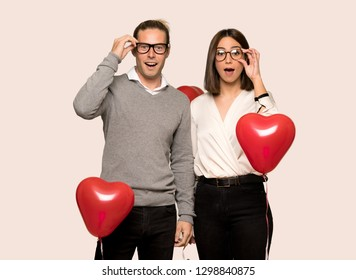 Couple in valentine day with glasses and surprised over isolated background