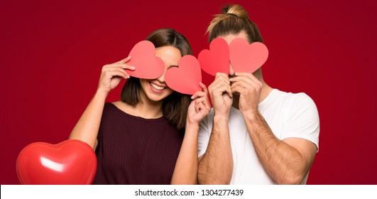 Couple in valentine day holding a heart symbol over red background
