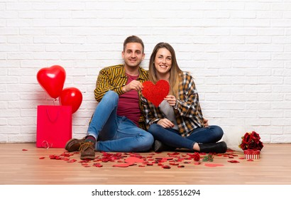 Couple in valentine day at indoors holding a heart symbol