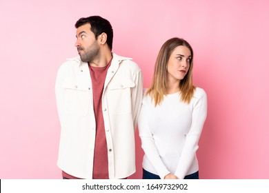 Couple in Valentine Day over isolated pink background nervous and scared